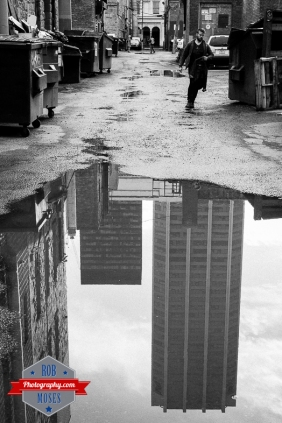 Downtown Calgary Alley puddle city reflection guy man street - Rob Moses Photography - Photographer famous 50L