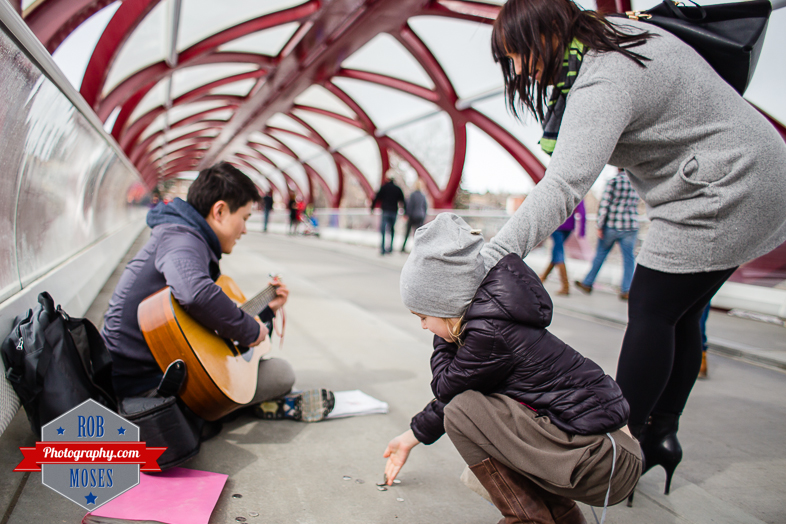 Calgary Alberta Skyline Street Photography - busking busker girl woman give money famous peace bridge bokeh guitar music musican - Rob Moses Photography - Vancouver Seattle Photographer Photographers-1.jpg-1