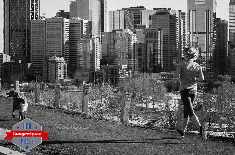 Woman girl run running jogging dog doggy Calgary Alberta Canada YYC Skyline urban metro buildings - Rob Moses Photography - Vancouver Seattle Photographer - Famous Pentax 50mm - Street Photographers Path Trail-1