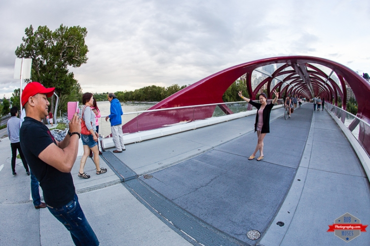 YYC woman man Peace Bridge fisheye uran modern people street picture phone - Rob Moses Photography - Vancouver Seattle Calgary Photographer Photographer Native American Famous Tlingit Ojibawa Top Popular Best Canadian Lifestyle