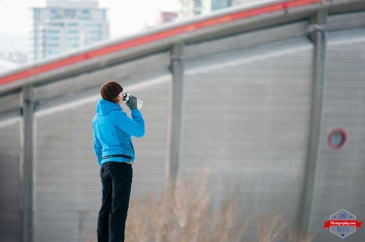 YYC woman drinking coffee saddledome bokeh city life winter Rob Moses Photography Calgary Photographer Photographers Native American Famous un celebrity Tlingit Ojibawa Top Popular Best Good Canadian