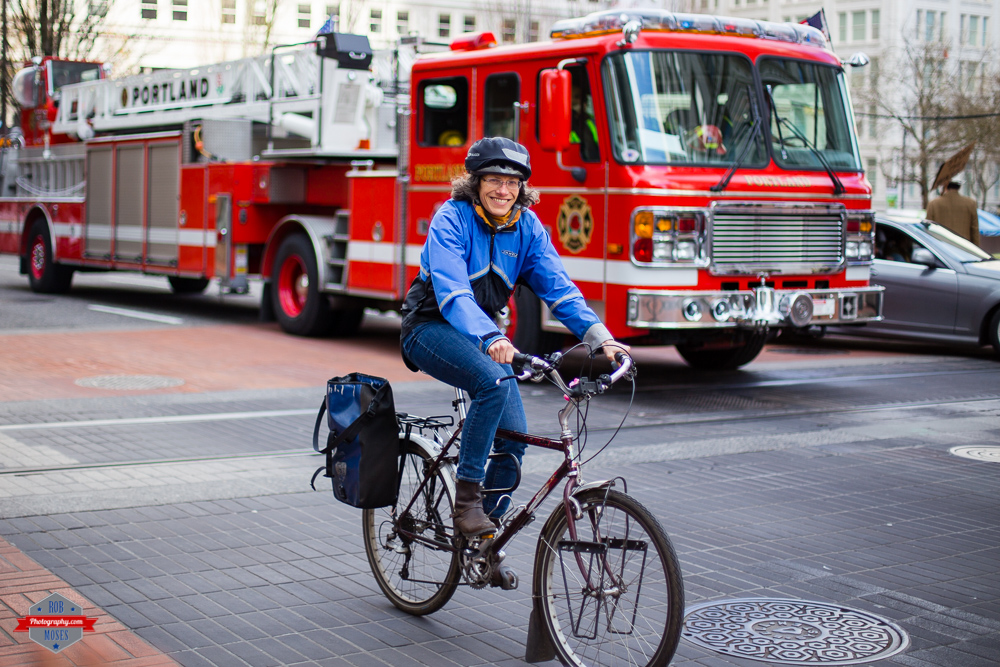 street cycling bike woman happy smile fire truck Rob Moses Photography Portland Calgary Vancouver Seattle Spokane Photographer WA BC Native American Tlingit Ojibaway famous un celebrity Canadian best pdx